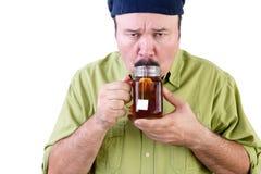 品尝杯子在白色的清凉茶的缺乏信心的人 免版税库存照片