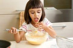品尝混合物的愉快的小女孩烹调蛋糕 库存图片