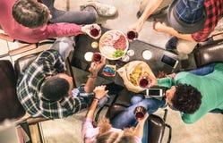 品尝红葡萄酒的多种族朋友顶视图在酒吧酿酒厂 库存图片