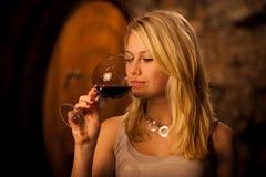 品尝红葡萄酒的美丽的年轻白肤金发的妇女在葡萄酒库里 免版税图库摄影