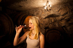 品尝红葡萄酒的美丽的年轻白肤金发的妇女在葡萄酒库里 库存图片