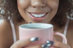 品尝茶的快乐的女孩 免版税图库摄影