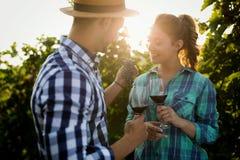 品尝酒的人们在葡萄园里 免版税库存图片