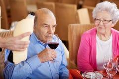 品尝酒的老人在餐馆 免版税图库摄影