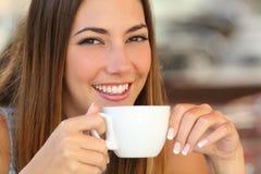 品尝从一个杯子的妇女一份咖啡在餐馆大阳台 免版税库存图片