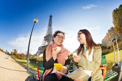 品尝macarons的两个朋友在艾菲尔铁塔附近 图库摄影