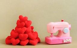 织品心脏式样桃红色缝纫机和堆  免版税库存图片