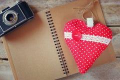 织品心脏的顶视图图象,葡萄酒照片照相机和打开在木桌上的空白的笔记本 情人节庆祝概念 免版税图库摄影