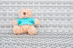 织品熊玩偶坐与拷贝空间的木织法椅子纹理背景的特写镜头 免版税图库摄影