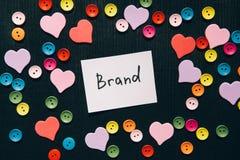 品牌-在黑背景与五颜六色的心脏装饰,企业概念的词 库存图片