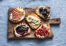 品种烤面包点心小板材三明治用乳脂干酪和苹果,石榴,果酱,葡萄,花生酱,香蕉 免版税库存照片