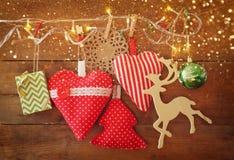 织品红色心脏和树的圣诞节图象 木驯鹿和诗歌选光,垂悬在蓝色木backgro前面的绳索 免版税库存图片
