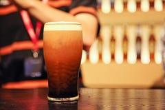品脱在柜台的啤酒与背景的人 免版税库存照片