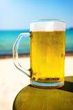 品脱在海滩桌顶部的冰镇啤酒 免版税库存图片
