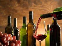 品酒大气在倒在一块玻璃的酿酒厂地窖里红葡萄酒在酒瓶前面 图库摄影