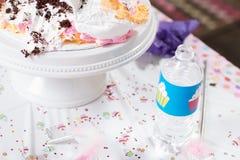 哄骗与乳脂状的蛋糕的生日聚会桌 免版税库存照片