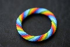 哄骗从彩虹颜色小珠的` s镯子在黑暗的背景的 图库摄影