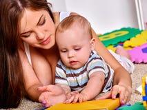 哄骗使用与在地板上的难题玩具的男婴 库存图片