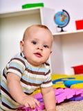 哄骗使用与在地板上的难题玩具的男婴 库存照片
