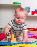 哄骗使用与在地板上的难题玩具的男婴 免版税库存照片