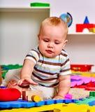 哄骗使用与在地板上的难题玩具的男婴 免版税库存图片