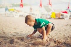 哄骗使用与坐户外在Pebble海滩的玩具汽车 库存照片