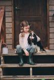哄骗使用与她的西班牙猎狗狗的女孩,坐台阶在木原木小屋 库存照片
