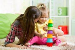哄骗使用与杯子玩具的女孩和母亲 免版税库存图片