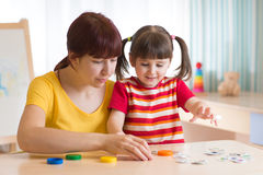 哄骗使用与难题玩具一起的女孩和母亲 免版税图库摄影