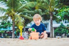 哄骗使用在与儿童` s铁锹和桶的海滩 图库摄影