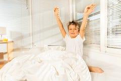 哄骗做他的早晨锻炼的男孩坐在床上 库存照片