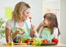 哄骗吃健康食物菜的女孩和母亲 库存照片