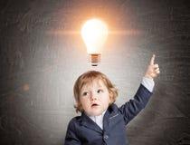 哄骗和在黑板的一个大橙色光电灯泡 免版税库存照片
