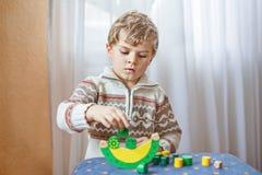 哄骗在家使用与木平衡玩具的男孩 免版税库存照片