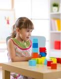 哄骗在家演奏木玩具或幼儿园的小女孩 图库摄影