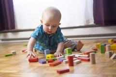 哄骗在家演奏木玩具或托儿所的小孩 免版税库存照片