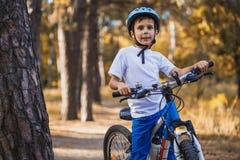 哄骗在循环户外在盔甲的晴朗的森林男孩的一辆自行车 库存照片