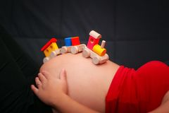 哄骗在怀孕的腹部的木火车玩具 浓缩婴孩的期望 库存照片