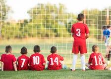 哄骗坐在目标观看的足球比赛后的足球运动员 库存图片