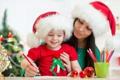 哄骗女孩和母亲文字信件对圣诞老人 免版税库存图片
