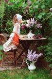 哄骗女孩在庭院茶会在与丁香紫丁香属植物花束的春日  库存照片