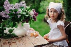 哄骗女孩在庭院茶会在与丁香紫丁香属植物花束的春日  图库摄影