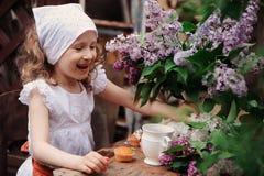 哄骗女孩在庭院茶会在与丁香紫丁香属植物花束的春日  免版税库存图片
