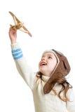 哄骗女孩穿戴的试验盔甲和使用与木飞机 免版税库存照片