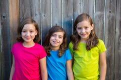 哄骗女孩画象微笑在灰色篱芭的姐妹和朋友 免版税库存图片