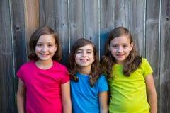 哄骗女孩画象微笑在灰色篱芭的姐妹和朋友 免版税图库摄影