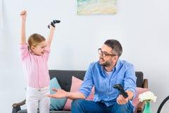 哄骗庆祝成功,当打电子游戏与父亲一起时 免版税库存图片