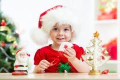 哄骗拿着圣诞节曲奇饼的圣诞老人帽子的女孩 免版税库存图片