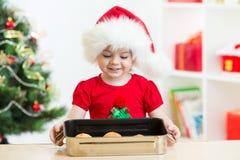 哄骗拿着圣诞节曲奇饼的圣诞老人帽子的女孩 免版税库存照片