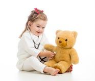 哄骗有使用与玩具的医生衣裳的女孩 图库摄影